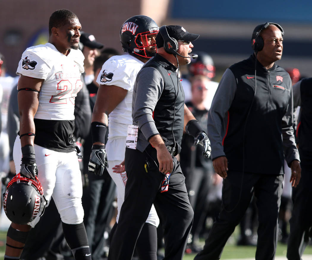 UNLV Rebels defensive line coach Tony Samuel, right, and head coach Tony Sanchez coach from the sideline as defensive back Greg Francis (23) looks on during the first half of their game in Reno, N ...