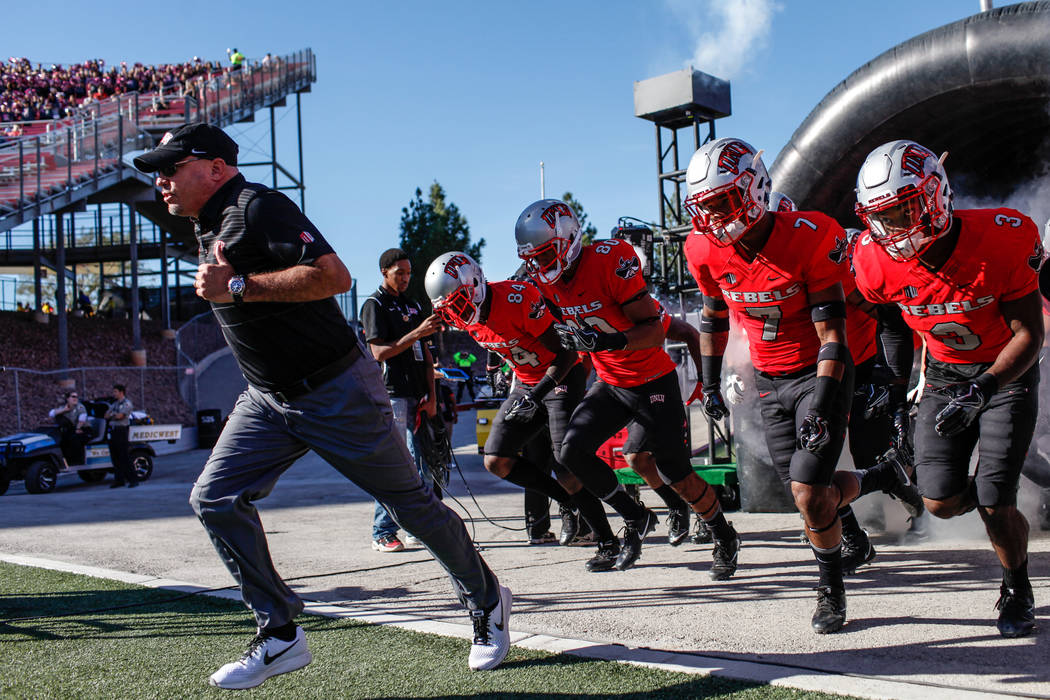 UNLV Rebels head coach Tony Sanchez and his team run onto the field before the start of a football game against Utah State Aggies at Sam Boyd Stadium in Las Vegas, Saturday, Oct. 21, 2017. Joel An ...