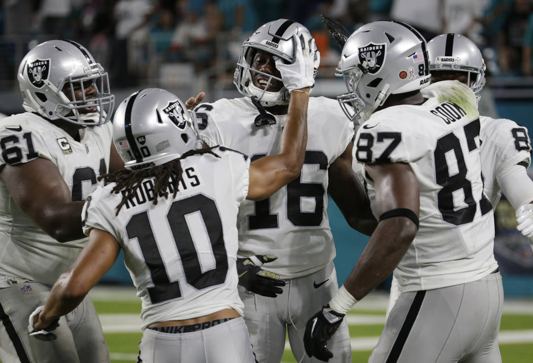 Oakland Raiders center Rodney Hudson, wide receiver Seth Roberts, and tight end Jared Cook, congratulate wide receiver Johnny Holton, after Holton scored a touchdown during