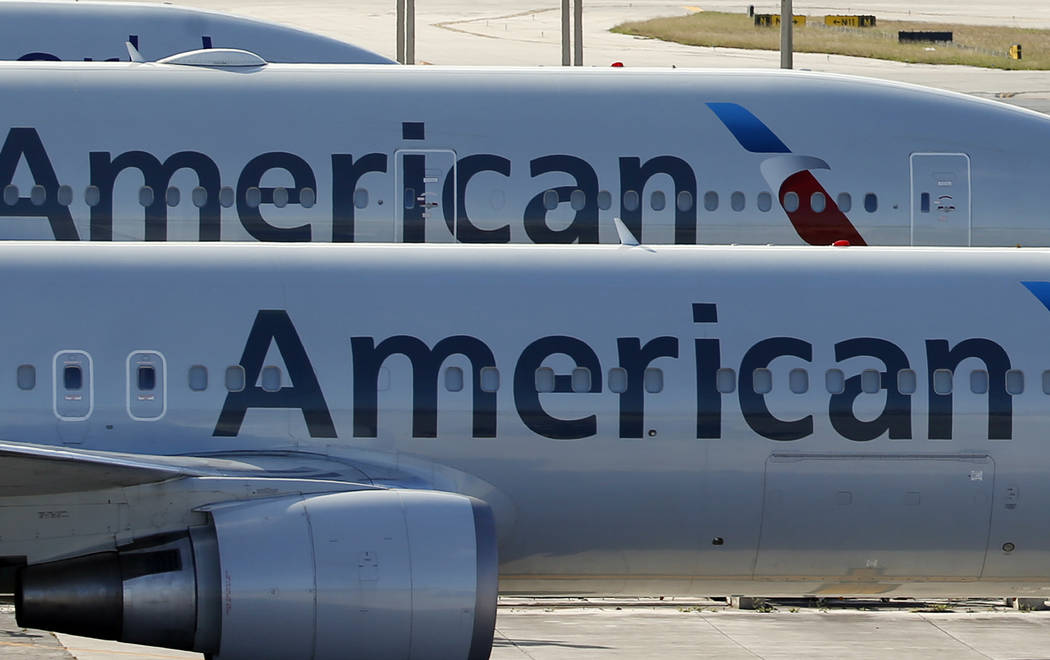 A pair of American Airlines jets are parked on the airport apron at Miami International Airport in Miami, Monday, Nov. 6, 2017. (AP Photo/Wilfredo Lee, File)