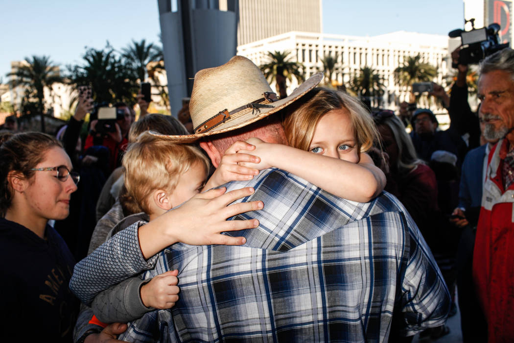 Ammon Bundy embraces his children outside the Lloyd George U.S. Courthouse in Las Vegas, after being released from custody Thursday, Nov. 30, 2017. Bundy's trial related to a 2014 Bunkerville stan ...