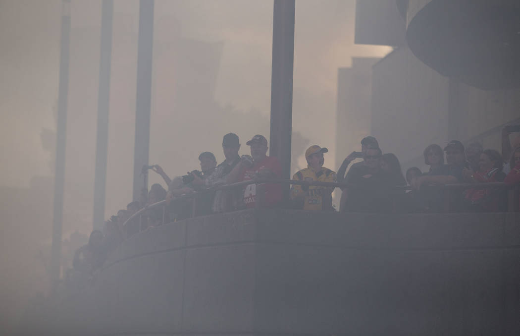 Race car fans watch through the smoke as drivers burn out on the Vegas Strip during NASCAR's Victory Lap on Wednesday, Nov. 29, 2017.  Richard Brian Las Vegas Review-Journal @vegasphotograph