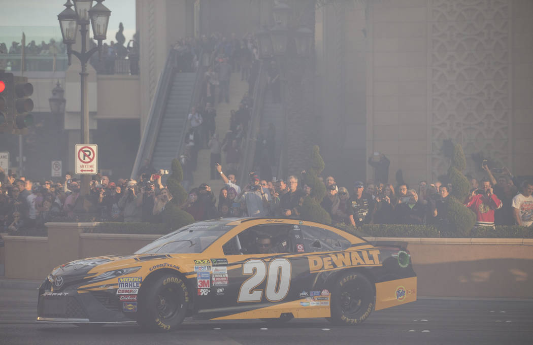 Race car driver Matt Kenseth (20) drives through a cloud of smoke on the Vegas Strip during NASCAR's Victory Lap on Wednesday, Nov. 29, 2017.  Richard Brian Las Vegas Review-Journal @vegasphotograph