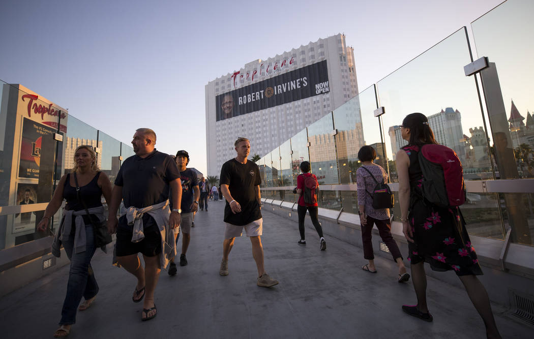 People walk over a pedestrian bridge linking MGM Grand and Tropicana hotel-casino near the intersection of Las Vegas Boulevard and Tropicana Avenue in Las Vegas, Thursday, Oct. 12, 2017. Richard B ...