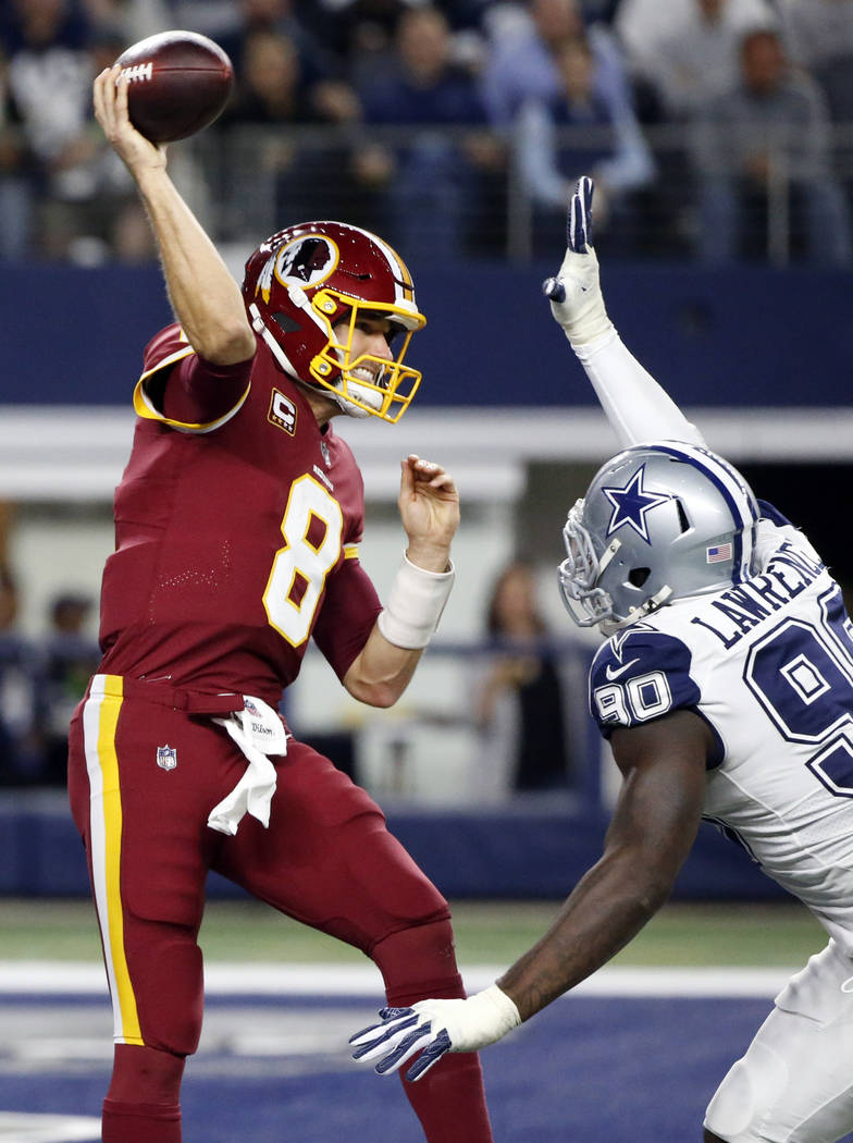 Washington Redskins quarterback Kirk Cousins (8) throws a pass under pressure from Dallas Cowboys defensive end DeMarcus Lawrence (90) in the first half of an NFL football game, Thursday, Nov. 30, ...