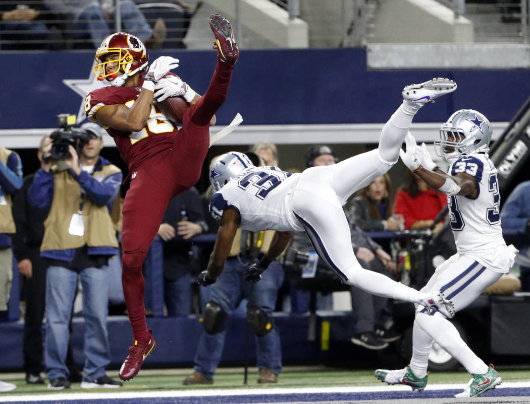 Washington Redskins' Josh Doctson (18) comes down with a touchdown catch in front of Dallas Cowboys safety Byron Jones (31) and Chidobe Awuzie (33) in the second half of an NFL football game, Thur ...
