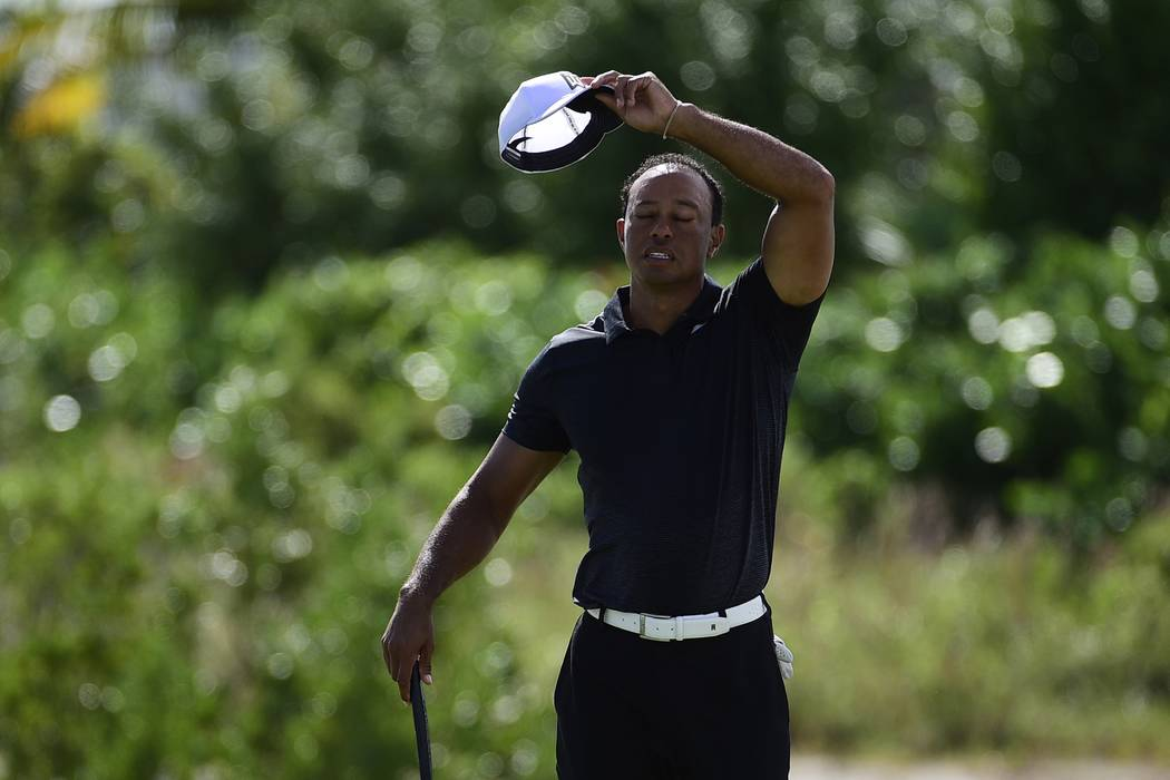 Tiger Woods wipes sweat from his face before teeing off on the fifth hole at the Hero World Challenge golf tournament at Albany Golf Club in Nassau, Bahamas, Thursday, Nov. 30, 2017. (AP Photo/Dan ...