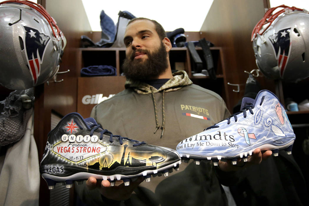 In this Wednesday, Nov. 29, 2017, photo New England Patriots defensive end Lawrence Guy displays cleats that honor victims of the Oct. 2017 Las Vegas shooting, left, and families who have lost an  ...
