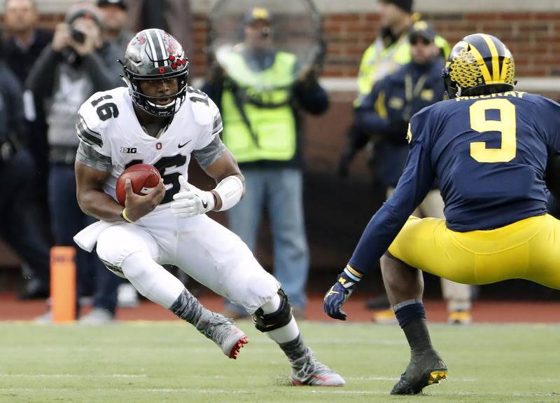 Nov 25, 2017; Ann Arbor, MI, USA; Ohio State Buckeyes quarterback J.T. Barrett (16) cuts on Michigan Wolverines linebacker Mike McCray (9) during the first half at Michigan Stadium. Mandatory Cred ...