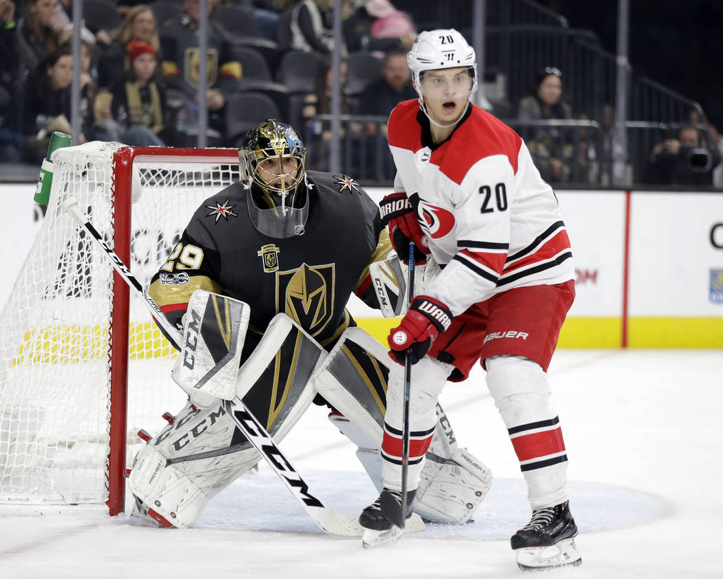 Carolina Hurricanes right wing Sebastian Aho (20) and Vegas Golden Knights goalie Marc-Andre Fleury watch play during the second period of an NHL hockey game Tuesday, Dec. 12, 2017, in Las Vegas.  ...