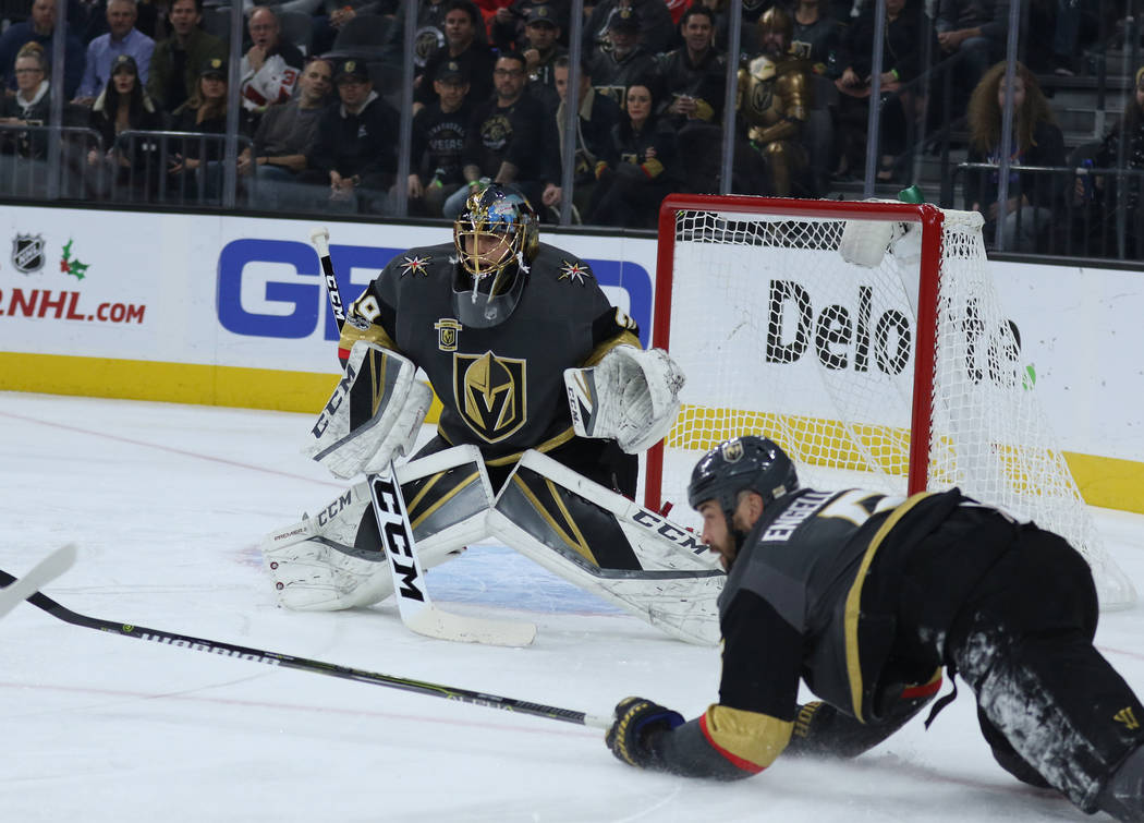Vegas Golden Knights defenseman Deryk Engelland (5) dives near Vegas Golden Knights goalie Marc-Andre Fleury (29) as he watches for the Carolina Hurricanes to attempt a goal during the first perio ...