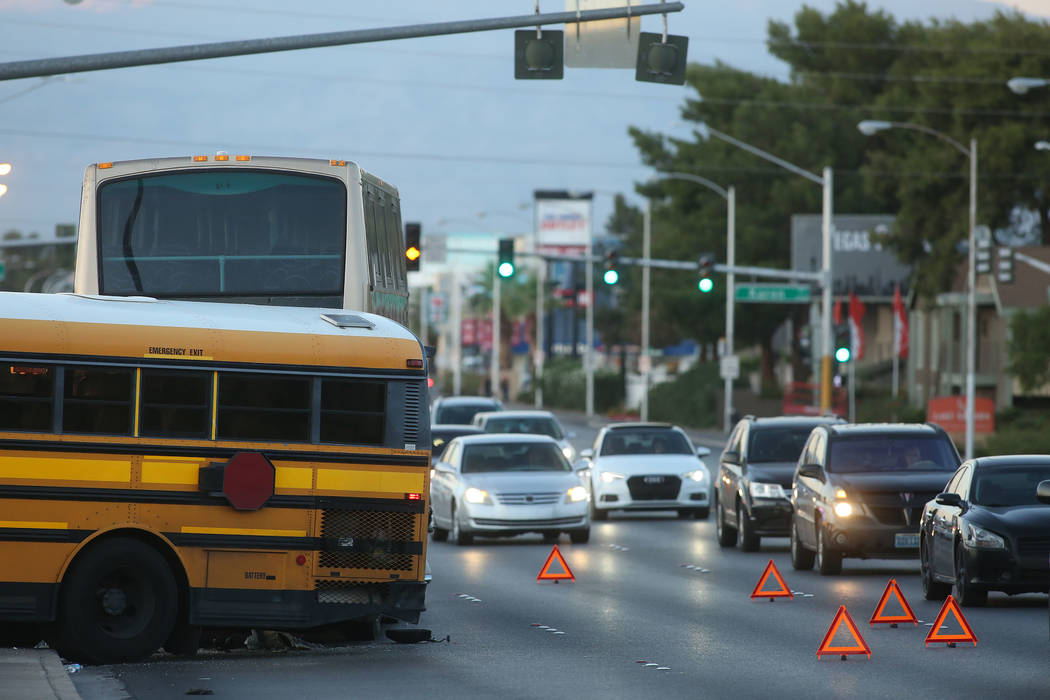 Debris lies beneath a Clark County School District bus after an accident near the intersection of South Eastern Avenue and East Karen Avenue, outside Valley High School, in Las Vegas, Thursday, Oc ...
