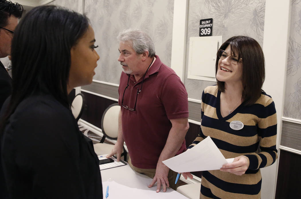 Jeff Ulriksen, center, shift manager at Outbound Call, and Elisha Meek, right, talk to job seekers, including Michelle Hall, left, during a hiring event at Palace Station on Thursday, Nov.16, 2017 ...