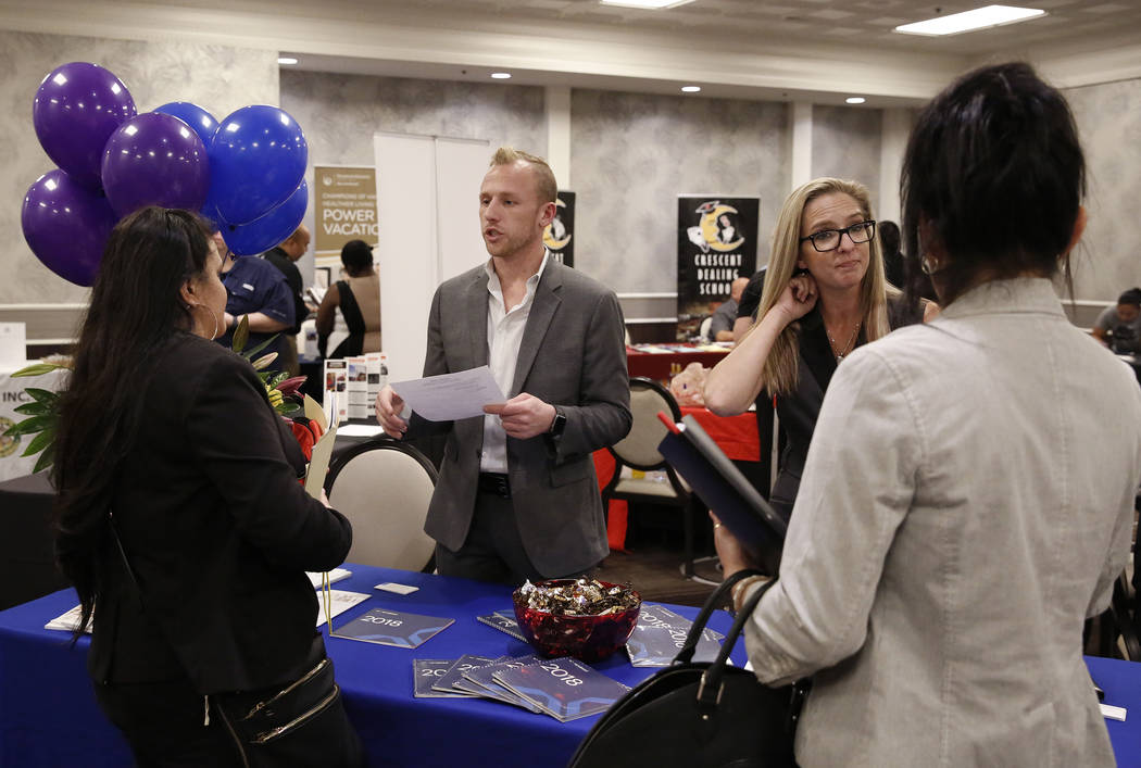 Corey Gerwaski, second left, marketing manager at Randstad, and Heather French of Randstad, second right, talk to job seekers, including Mandrell Hahn, left, during a hiring event at Palace Statio ...