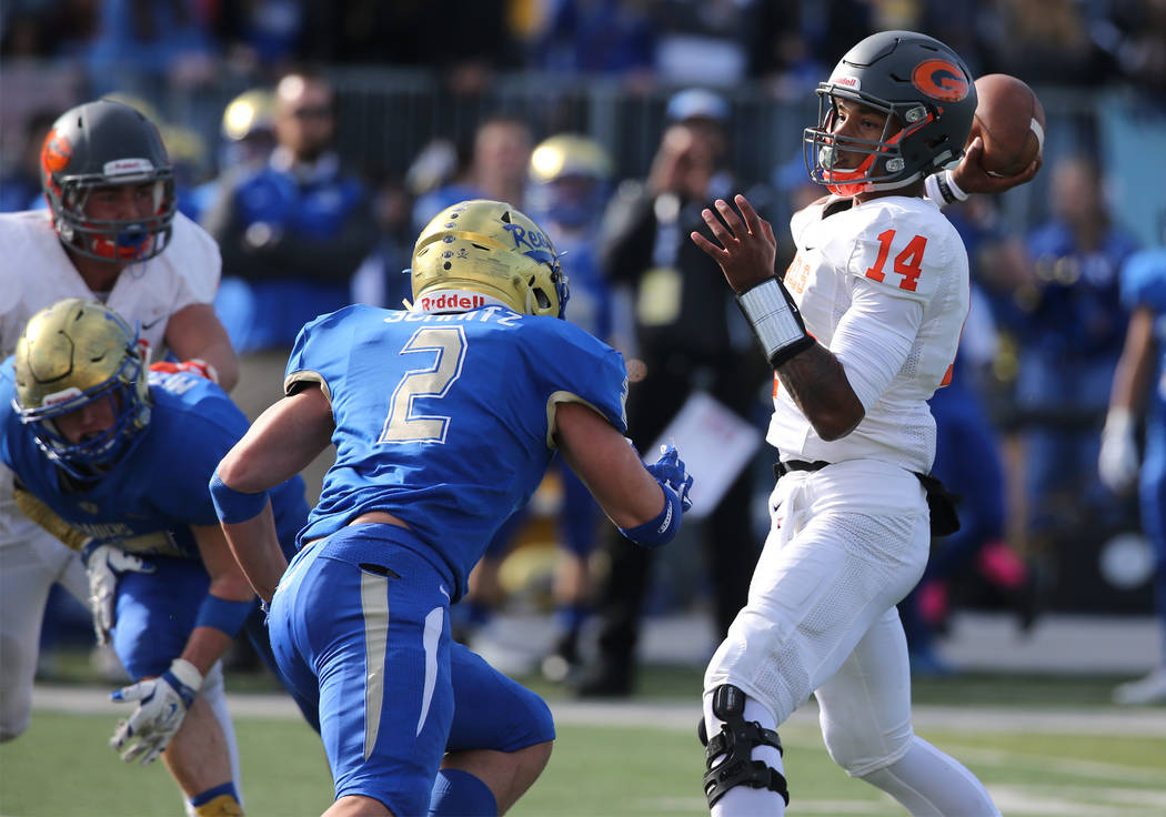 Bishop Gorman's Dorian Thompson-Robinson throws under pressure from Reed's Eric Schmitz Moran during the NIAA 4A state championship football game in Reno, Nev., on Saturday, Dec. 2,  ...