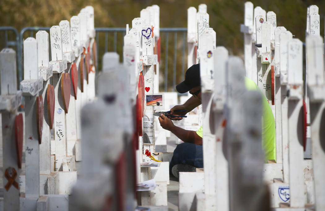 "Volunteer Steve Round works on removing items from the crosses that were moved from a makeshift memorial at the ""Welcome to Fabulous Las Vegas Sign"" to the Clark County Museum in ..."