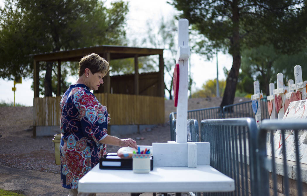 """Terri Chapman of Henderson takes in the crosses that were moved from a makeshift memorial at the """"Welcome to Fabulous Las Vegas Sign"""" to the Clark County Museum in Henderson on W ..."""