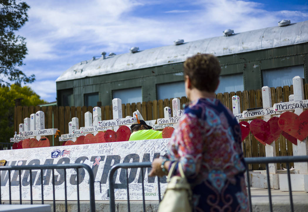 """Terri Chapman of Henderson watches as volunteer Steve Round works on removing items from the crosses that were moved from a makeshift memorial at the """"Welcome to Fabulous Las Vegas Sign&a ..."""