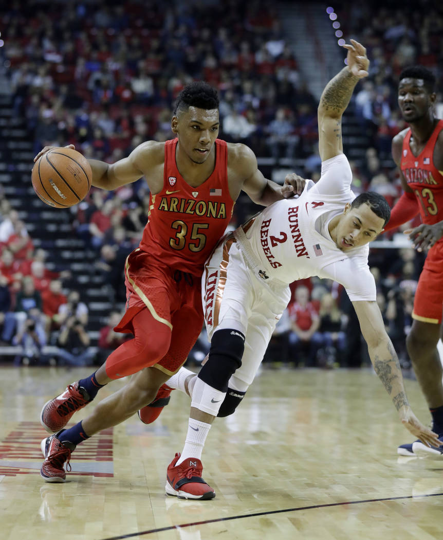 Arizona's Allonzo Trier (35) drives on UNLV's Anthony Smith during the first half of an NCAA college basketball game Saturday, Dec. 2, 2017, in Las Vegas. (AP Photo/Isaac Brekken)