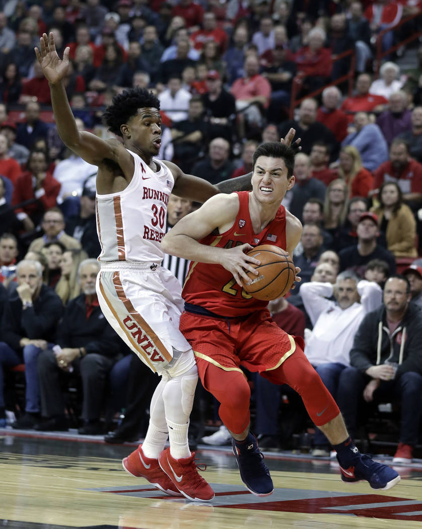 Arizona's Alex Barcello drives past UNLV's Jovan Mooring during the first half of an NCAA college basketball game Saturday, Dec. 2, 2017, in Las Vegas. (AP Photo/Isaac Brekken)