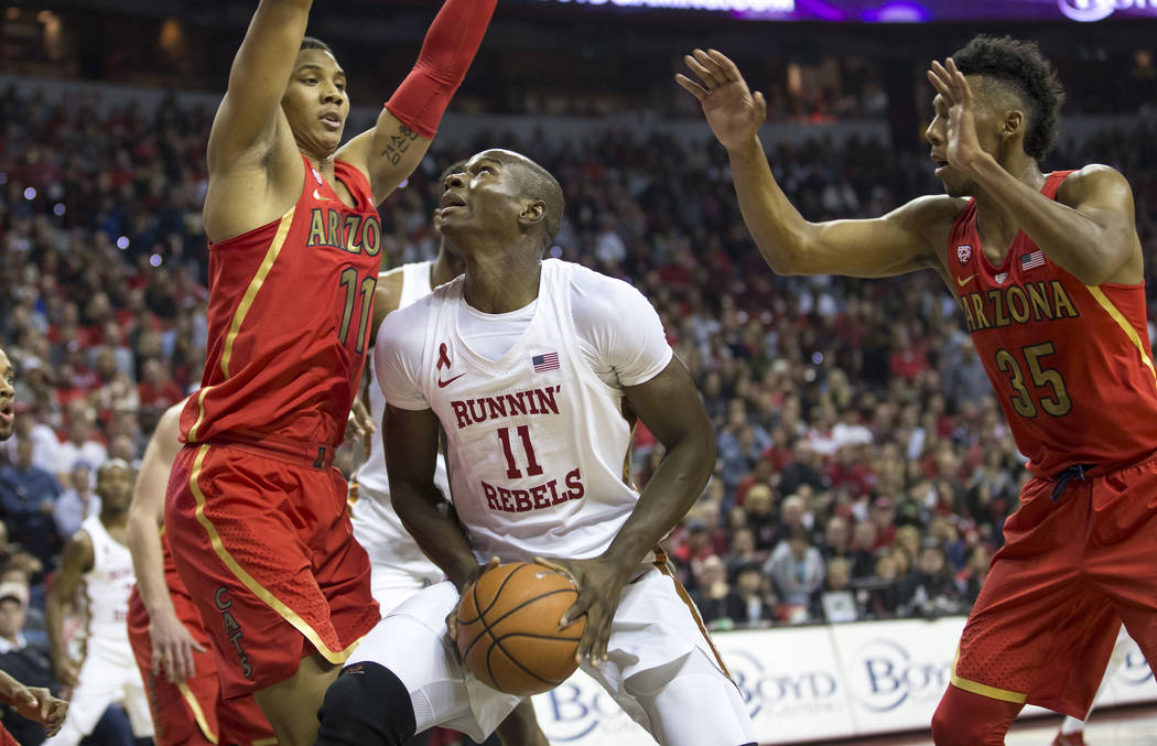 UNLV Rebels forward Cheickna Dembele (11) looks for a shot under pressure from Arizona Wildcats forward Ira Lee (11) and guard Allonzo Trier (35) during the first half of an NCAA college basketbal ...