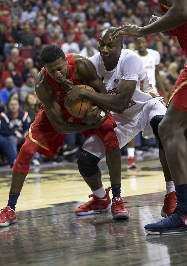 Arizona Wildcats guard Dylan Smith, left, and UNLV Rebels forward Cheickna Dembele (11) fight for the ball during the first half of an NCAA college basketball game at Thomas & Mack Center in L ...
