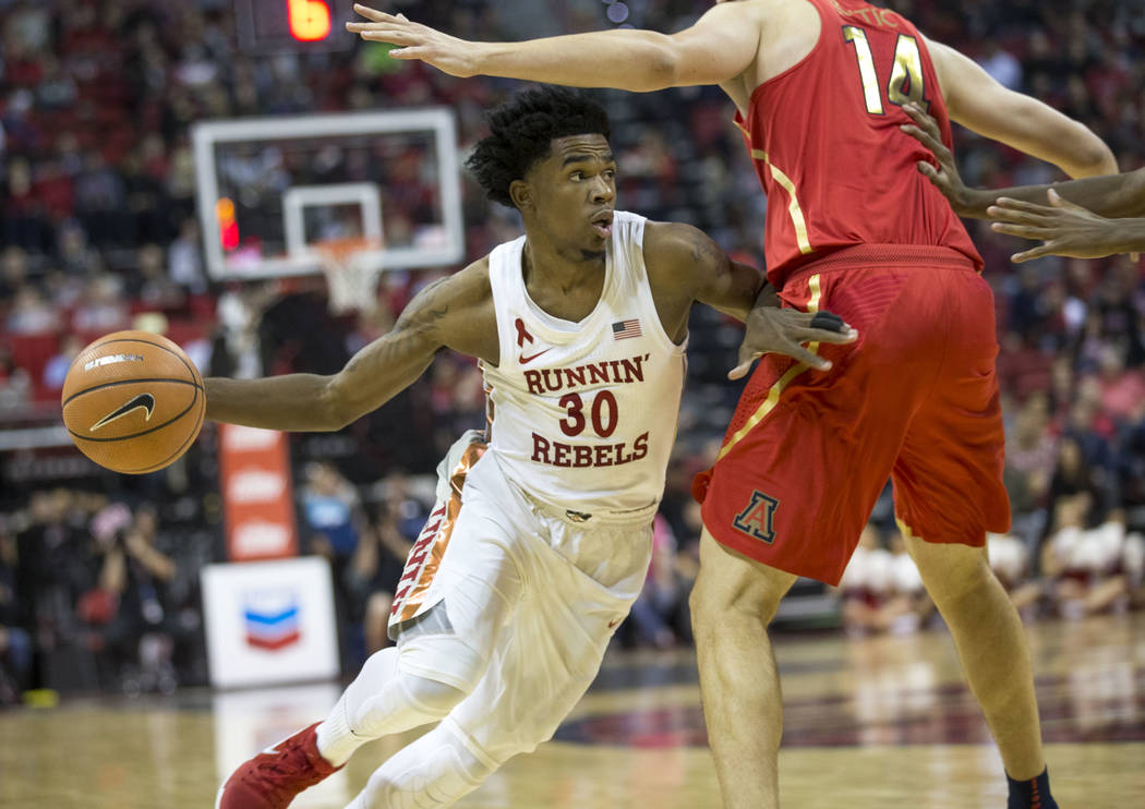 UNLV Rebels guard Jovan Mooring (30) dribbles past Arizona Wildcats center Dusan Ristic (14) during the second half of an NCAA college basketball game at Thomas & Mack Center in Las Vegas on S ...