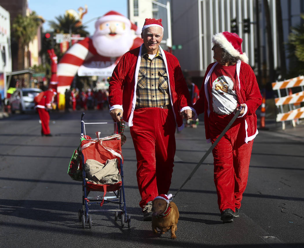 "Jim and Carol Nielsen walk with their dog ""Lil Dog"" during the Las Vegas Great Santa Run in downtown Las Vegas on Saturday, Dec. 2, 2017. Chase Stevens Las Vegas Review-Journal @ ..."