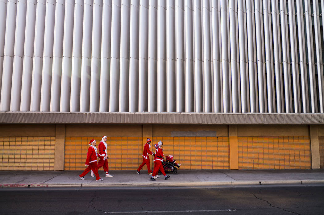 Race participants walk near the start area before the Las Vegas Great Santa Run in downtown Las Vegas on Saturday, Dec. 2, 2017. Chase Stevens Las Vegas Review-Journal @csstevensphoto