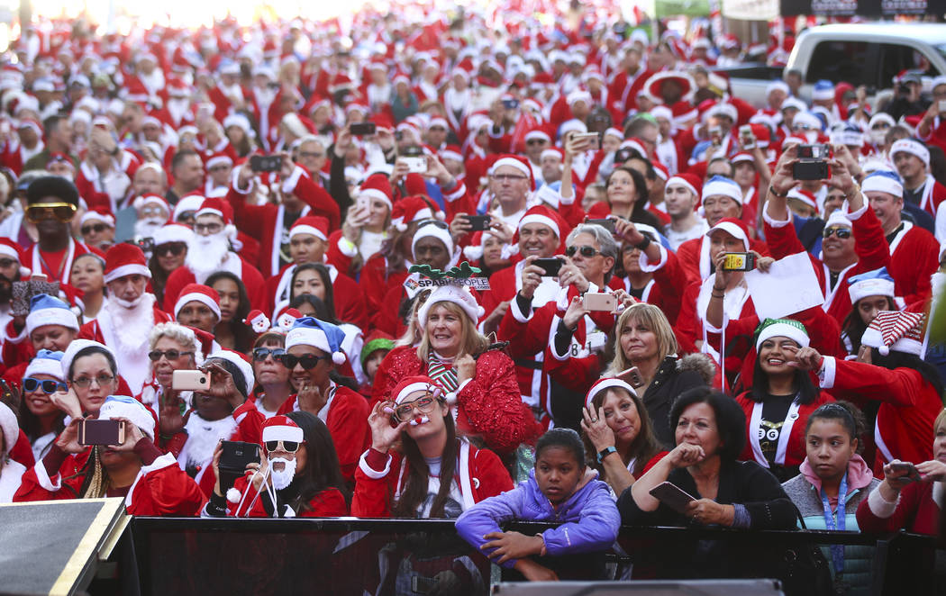 Race participants crowd around the 3rd Street Stage at the Fremont Street Experience before the start of the Las Vegas Great Santa Run in downtown Las Vegas on Saturday, Dec. 2, 2017. Chase Steven ...