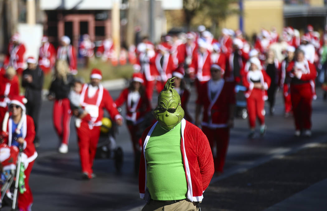 A man dressed as the Grinch joins race participants during the Las Vegas Great Santa Run in downtown Las Vegas on Saturday, Dec. 2, 2017. Chase Stevens Las Vegas Review-Journal @csstevensphoto