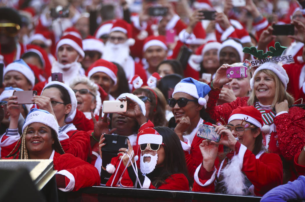 Race participants take photos at the 3rd Street Stage at the Fremont Street Experience before the start of the Las Vegas Great Santa Run in downtown Las Vegas on Saturday, Dec. 2, 2017. Chase Stev ...