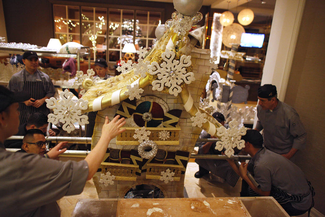 Extra hands from the kitchen assist to lift the giant house that will be the focal point of the winter village at the Four Seasons in Las Vegas, Tuesday, Nov. 21, 2017. Rachel Aston Las Vegas Revi ...