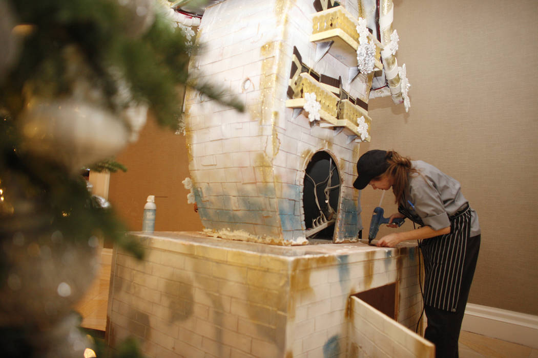 Pastry cook Courtney Williams hot glues pieces for the giant house that will be the focal point of the winter village at the Four Seasons in Las Vegas, Tuesday, Nov. 21, 2017. Rachel Aston Las Veg ...