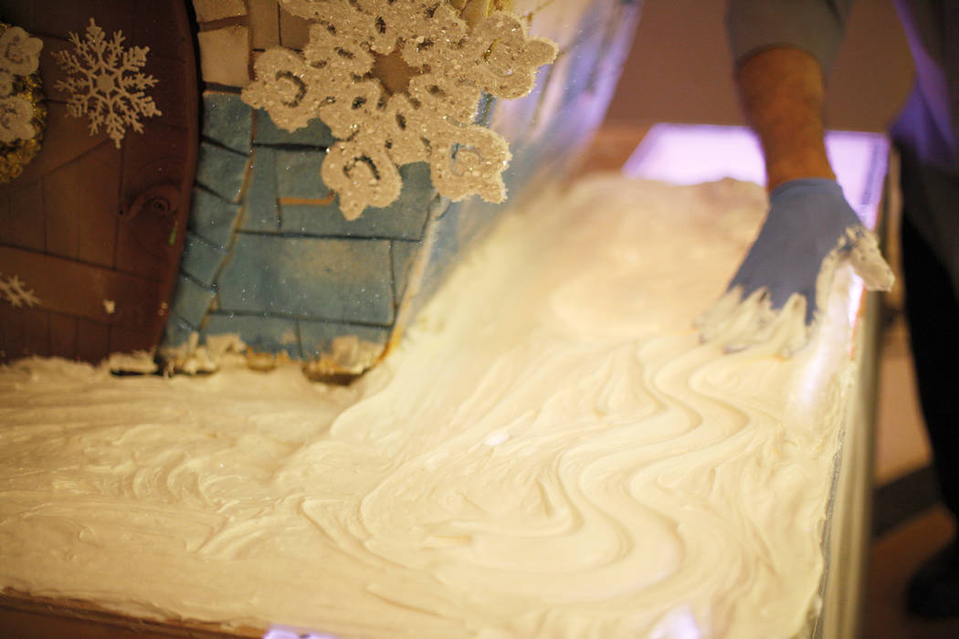 Pastry cook Frank Pedroza smooths out frosting at the base of the giant house that will be the focal point of the winter village at the Four Seasons in Las Vegas, Tuesday, Nov. 21, 2017. The frost ...