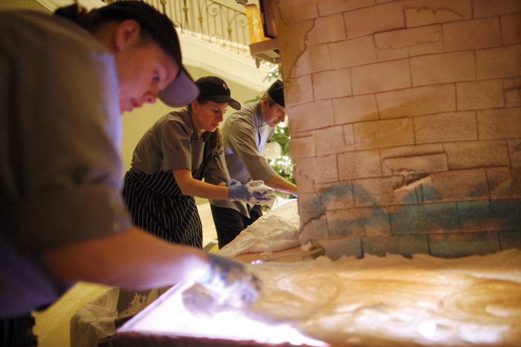 Pastry cook Mallory Jones, from left, pastry cook Courtney Williams, and pastry cook Frank Pedroza smooth out frosting at the base of the giant house that will be the focal point of the winter vil ...