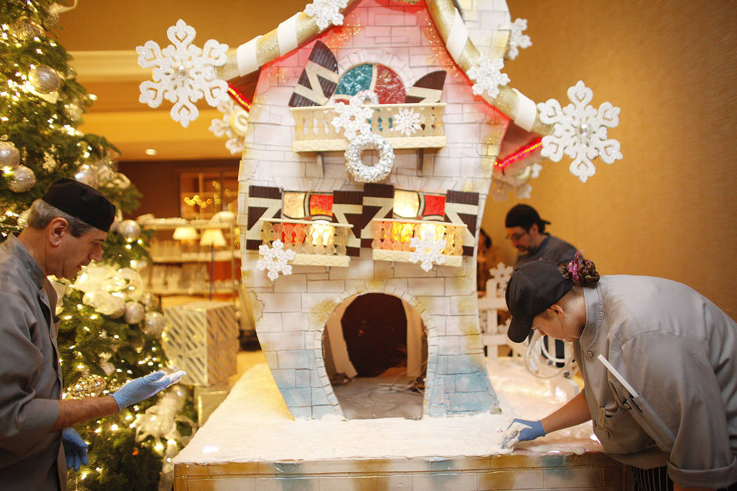 Pastry cook Frank Pedroza, left, and pastry cook Mallory Jones smooth out frosting at the base of the giant house that will be the focal point of the winter village at the Four Seasons in Las Vega ...