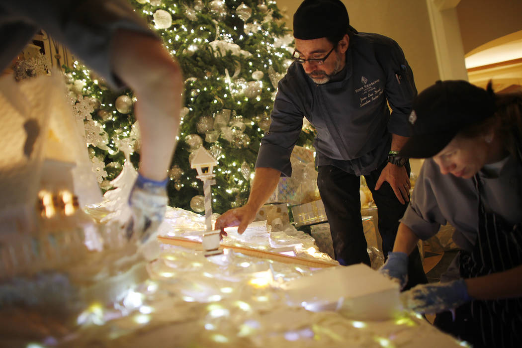 Executive Pastry Chef Jean-Luc Daul adds a street light made of fondant to the winter village as pastry cook Courtney Williams smooths out frosting at the Four Seasons in Las Vegas, Tuesday, Nov.  ...