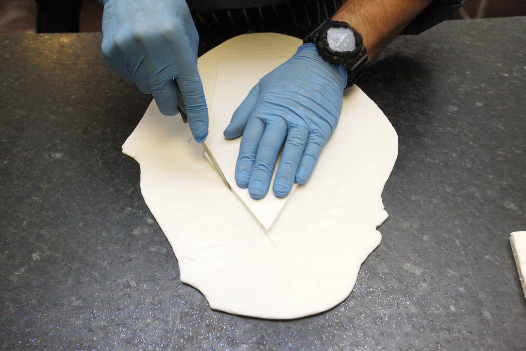 Executive Pastry Chef Jean-Luc Daul cuts part of a house out of sugar fondant for a winter village at the Four Seasons in Las Vegas, Tuesday, Nov. 14, 2017. Fondant is attached to foam board to ma ...