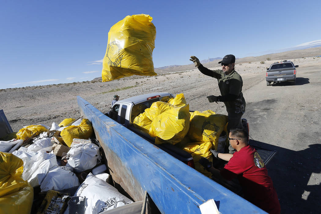 A Bureau of Land Management employee tosses a bag of trash into a roll-away dumpster during a volunteer cleanup hosted by the Bureau of Land Management at a popular target shooting area off South  ...