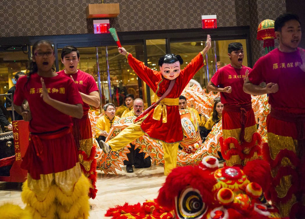 Members of the Lohan School of Shaolin, including Ronalli Enriquez dressed as Buddha, center, entertain the crowd with a traditional lion and dragon dance during the 1-year anniversary of the Luck ...