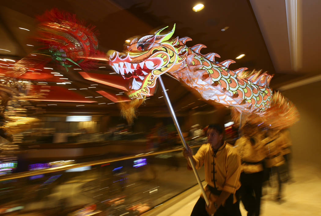 Oscar Cisneros, center, of the Lohan School of Shaolin entertains the crowd with a traditional lion and dragon dance during the 1-year anniversary of the Lucky Dragon in Las Vegas on Sunday, Dec.  ...