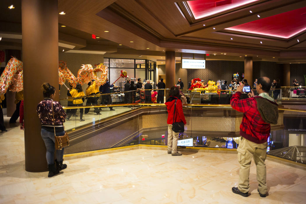 People watch as members of the Lohan School of Shaolin entertain the crowd with a traditional lion and dragon dance during the 1-year anniversary of the Lucky Dragon in Las Vegas on Sunday, Dec. 3 ...