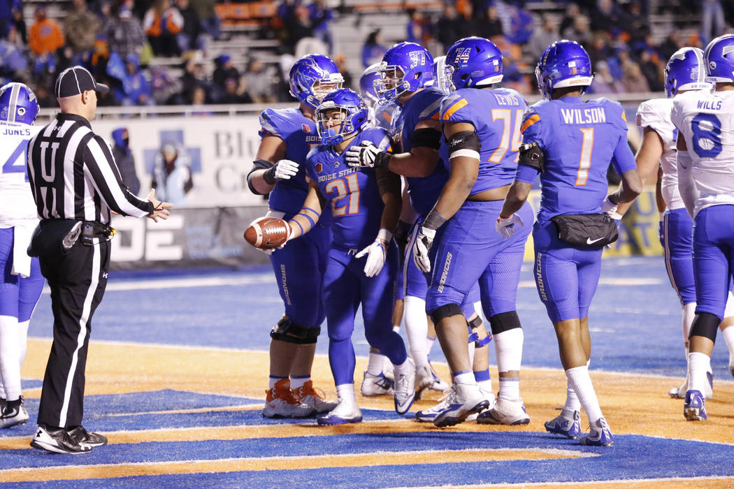 Boise State celebrates as running back Ryan Wolpin (21) hands over the ball after a touchdown during the second half of an NCAA college football game against Air Force in Boise, Idaho, Saturday, N ...
