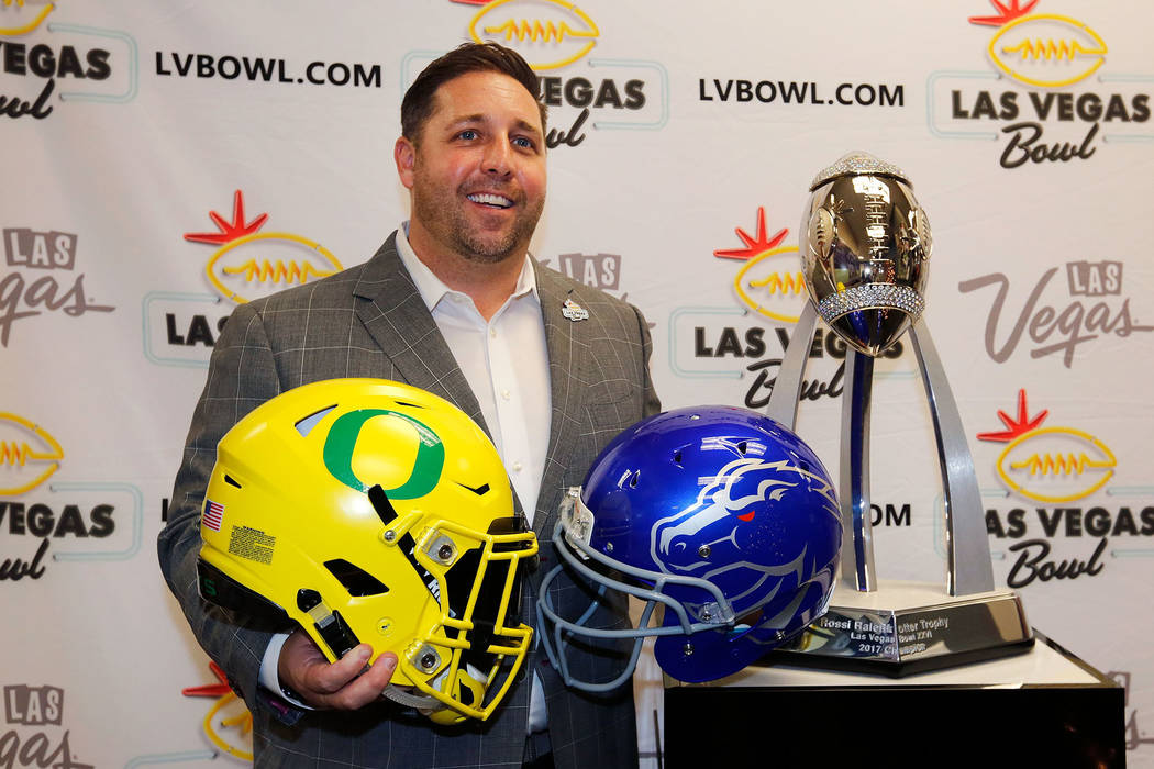 John Saccenti, Las Vegas Bowl executive director, holds football helmets of University Oregon and Boise State University during a news conference at his office in Las Vegas, Sunday, Dec. 3, 2017.  ...
