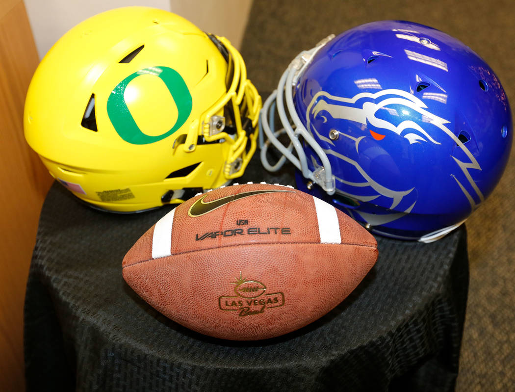 Football helmets of University Oregon and Boise State University at a news conference at the Las Vegas Bowl office in Las Vegas, Sunday, Dec. 3, 2017. Mountain West champion Boise State will play  ...