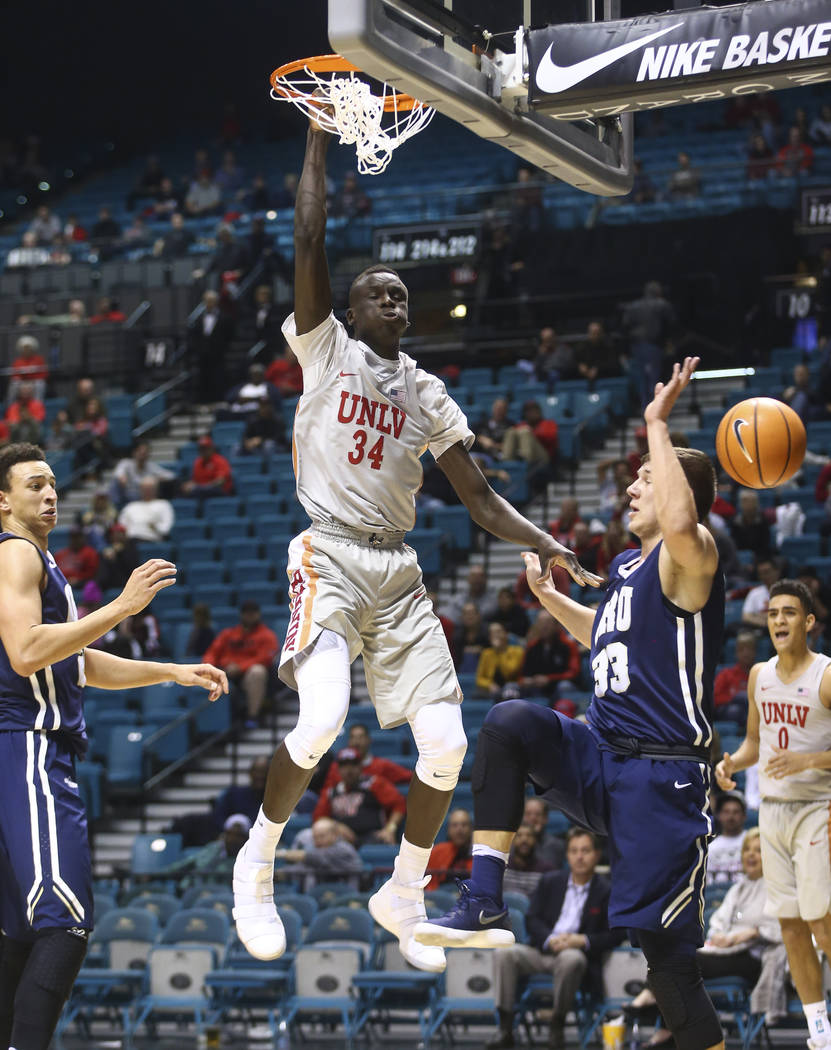 UNLV's Cheikh Mbacke Diong (34) dunks over Oral Roberts' Emir Ahmedic (33) during their basketball game at the MGM Grand Garden Arena in Las Vegas on Tuesday, Dec. 5, 2017. UNLV won 92-66. Chase S ...