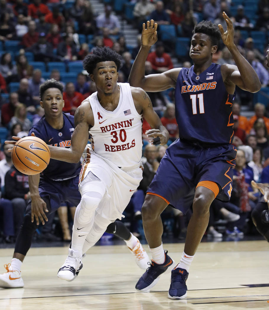 UNLV's Jovan Mooring passes the ball as he drives next to Illinois' Greg Eboigbodin during the first half of an NCAA college basketball game Saturday, Dec. 9, 2017, in Las Vegas. (AP Photo/John Lo ...