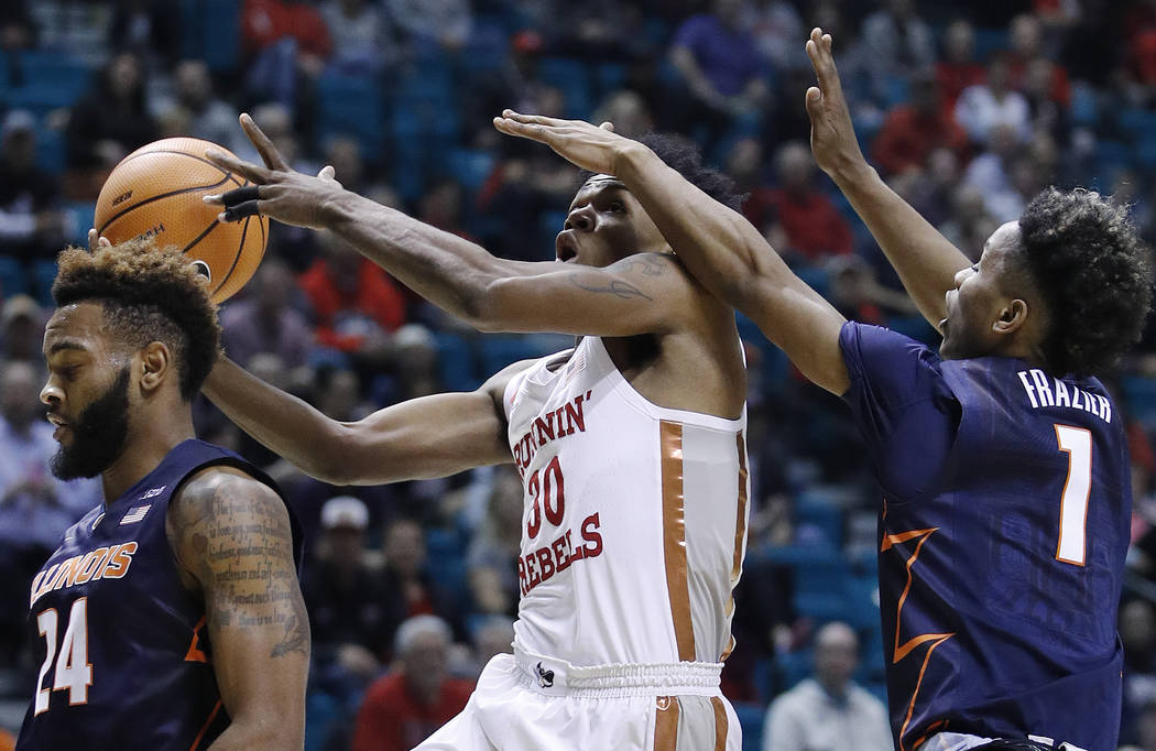 Illinois' Trent Frazier, right, fouls UNLV's Jovan Mooring during the first half of an NCAA college basketball game Saturday, Dec. 9, 2017, in Las Vegas. (AP Photo/John Locher)