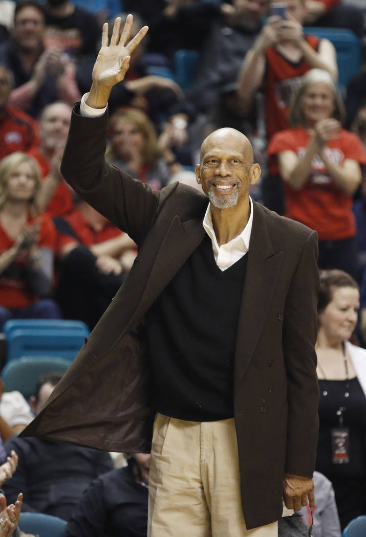 Retired NBA basketball player Kareem Abdul-Jabbar waves during an NCAA college basketball game between UNLV and Illinois, Saturday, Dec. 9, 2017, in Las Vegas. (AP Photo/John Locher)